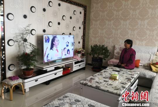 图为惠玉珠的妻子在客厅看电视。 刘玉桃 摄