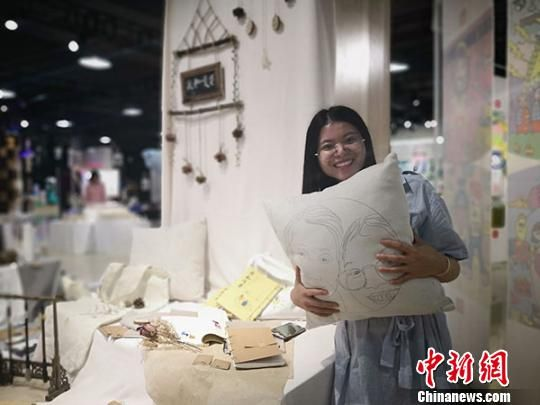 图为潘琼瑶抱着印有外婆和自己头像的毕业设计抱枕,介绍她和外婆生活的点点滴滴。 魏建军 摄