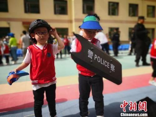"""图为幼儿园学生穿上特警""""装备"""",戴上头盔手握保护盾。 魏建军 摄"""