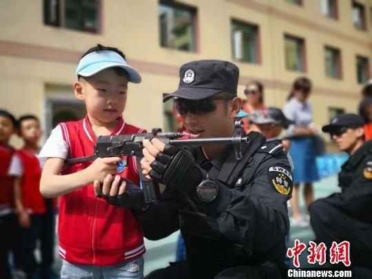 """图为特警队员指导幼儿园学生如何正确""""握枪""""。 魏建军 摄"""