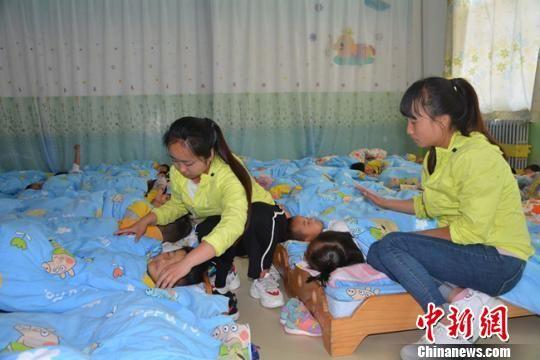 图为幼儿园老师照顾学生午休。 郭红 摄