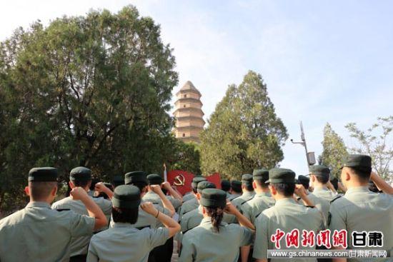图为2.机关干部在宝塔山上面对鲜红党旗庄严宣誓。万华锋 摄。