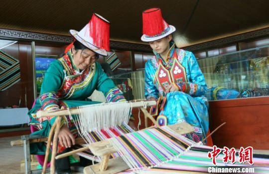 展厅工作人员正在向游客展示裕固族非物质文化遗产织褐子。 郭蓉 摄