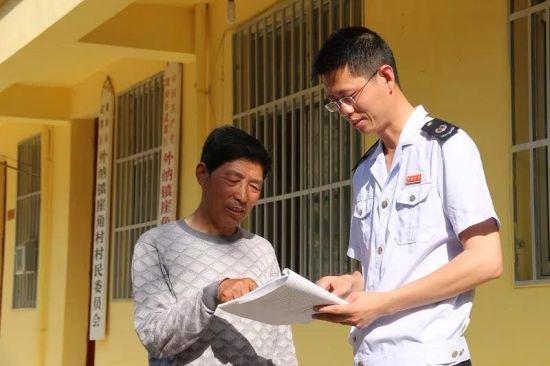 武都区国税局纪检组长杜淼给崖角村村长赵玉杰讲解税法。