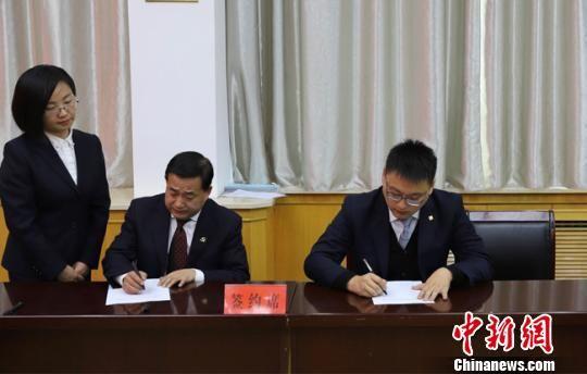 中国农业银行甘肃分行代表(左)与甘肃省农业信贷担保有限责任公司代表签署合作协议。(资料图) 柴金福 摄