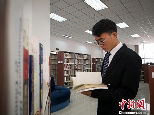 图为王满全在图书馆看书。 魏建军 摄