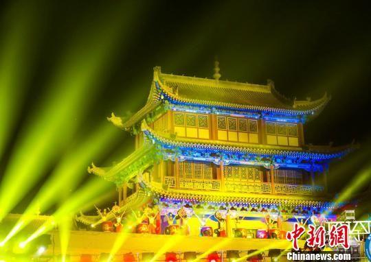 图为开幕式期间,在灯光交相辉映中的嘉峪关关城。 钟欣 摄