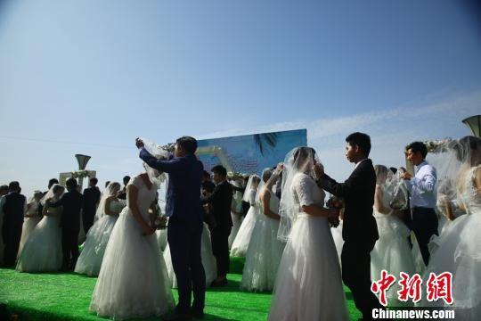 图为新郎揭开新娘面纱。 陈兴明 摄