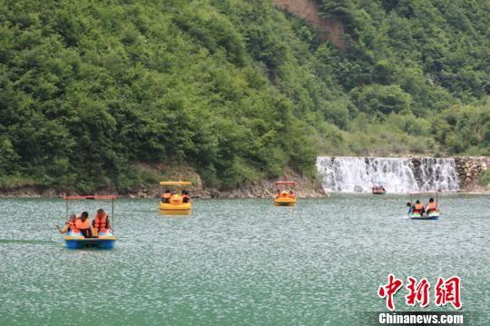 官鹅沟景区内,游客划船于湖里。 殷春永 摄