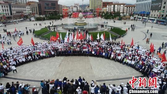 图为参与甘南行公益活动的医务专家、爱心人士、海外专家、媒体志愿者共千余人在甘南合作市合影。 钟欣 摄
