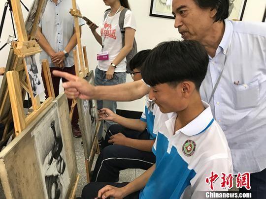 图为书画名家现场指导学生绘画技巧。 闫姣 摄