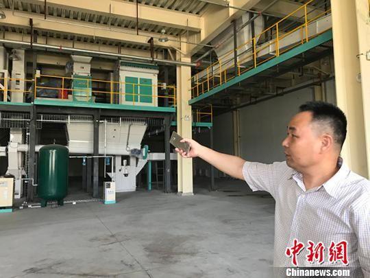 图为入驻兰州新区的企业负责人介绍用于粗加工进口粮食的自动化设备。 闫姣 摄