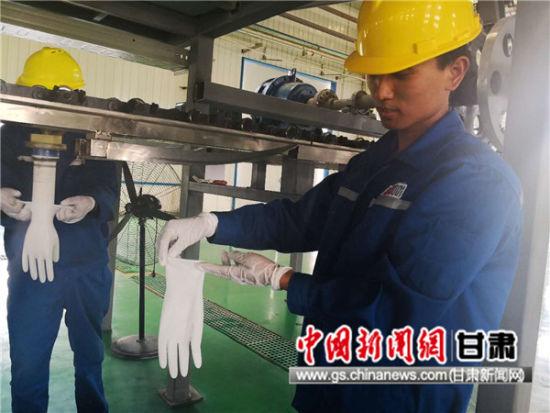 图为生产线工人展示水性聚氨酯外科手套。史静静 摄