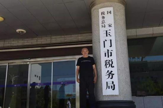 汪老在玉门市税务局牌前拍照留念。