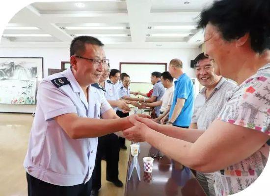 临泽县税务局联合党委委员与参加座谈会的离退休干部亲切握手。