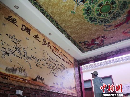 图为一家民宿将整面墙壁和屋顶装饰成丝绸之路路线图和莫高窟壁画,吸引游客驻足。 史静静 摄