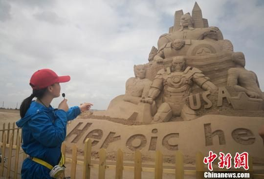 """图为导游介绍以""""漫威""""系列经典英雄动漫人物雕塑的""""复仇者""""。 魏建军 摄"""