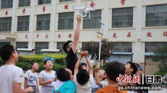 孩子们围观无人机的组装操作 。