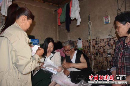图为社区工作人员上门帮助残疾老人常吉发办理临时救助。