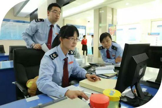龙国荣和办税厅工作人员一起审核办税资料