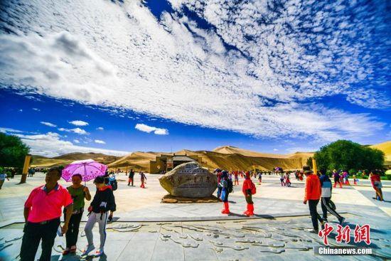 当地著名的鸣沙山月牙泉景区蓝天、白云、黄沙相映成趣,每天吸引数万中外游客观光游览。 王斌银 摄