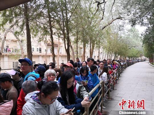 图为8月中旬,莫高窟前等候参观的应急游客排成近1公里长队。 冯志军 摄
