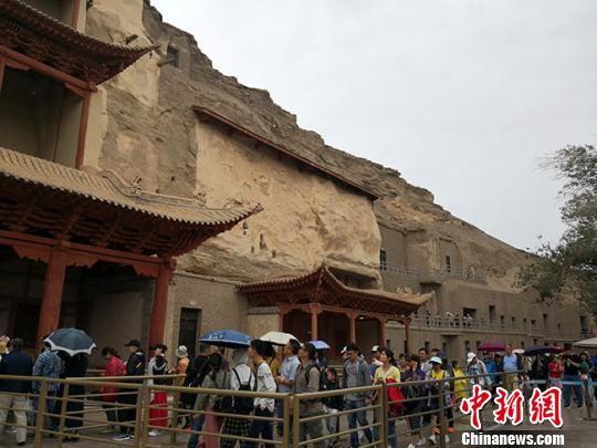 图为8月中旬,莫高窟九层楼前的游客如织。 冯志军 摄