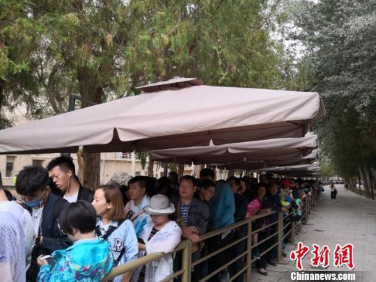 图为8月中旬,莫高窟前等候参观的应急游客排成近1公里的长队。 冯志军 摄