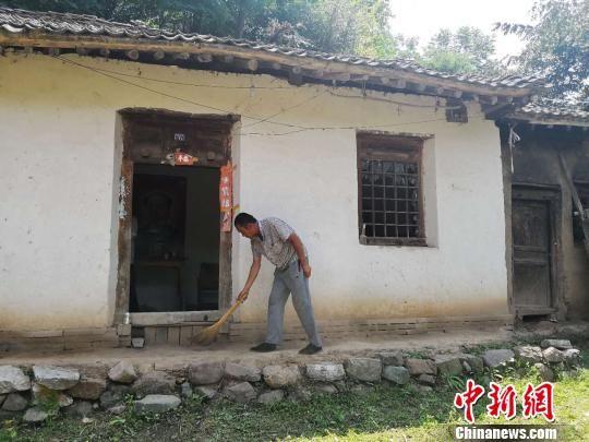 图为父亲杨立成打扫自家的两间土房。 史静静 摄