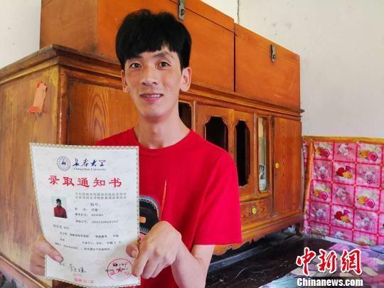 图为杨亮亮展示长春大学的录取通知书。 史静静 摄