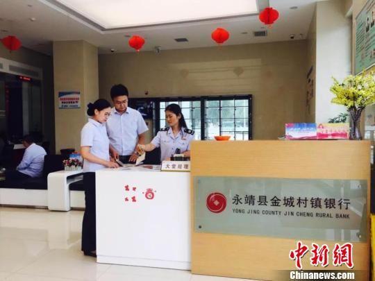 图为税务人员在永靖县金城村镇银行了解政策享受情况。国家税务总局甘肃省税务局供图