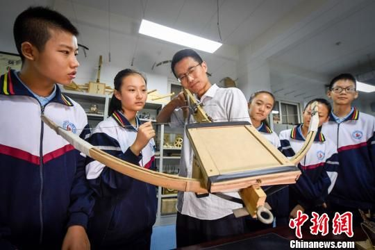 图为兰州市外国语中学的青年生物教师高飞指导学生们进行发明创造。 郁婕 摄