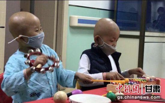 """""""音乐治疗""""是甘肃省红十字会推出的""""天使课堂""""系列活动之一,未来将普及甘肃省全省,致力让白血病患儿远离""""电子保姆"""",过上丰富多彩的童年生活。图为两名白血病患儿临时组成""""乐队""""演奏。闫姣 摄"""