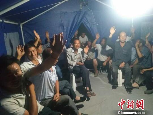 """图为果者村受灾群众每晚召开""""帐篷会议"""",乡村干部向群众讲解滑坡隐患和危险区域的危险性,劝导群众不得进入危险区域。(资料图) 钟欣 摄"""