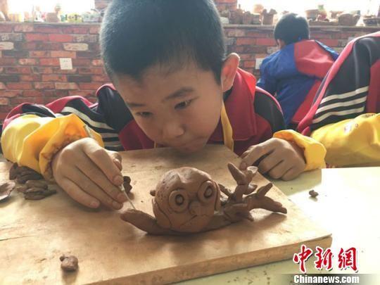 """实验三小陶艺课上,五年级学生王博文在自己作品上用木刀再加工,""""树干""""上显现出一条条纹路。 张婧 摄"""