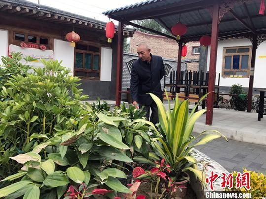 图为独石村村民张勤打理农家乐中的花卉。 艾庆龙 摄