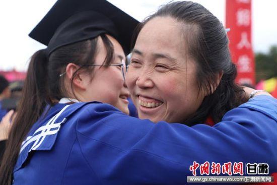 图为一名家长在成人礼上拥抱着已经长大成人的女儿,脸上露出幸福的笑容。 吴希会 摄