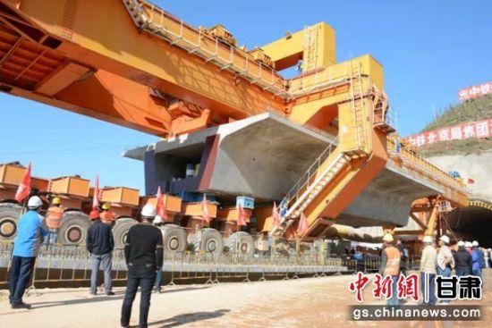图为架梁机缓缓地将近900吨的一榀箱梁铺装到位。李钊 摄