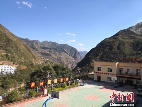 图为磨坝乡乡政府所在地,不远处是巍峨的大山。 杨娜 摄