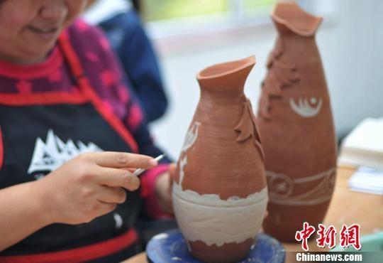 图为陶艺师使用马家窑纹样制作现代陶艺。 崔琳 摄