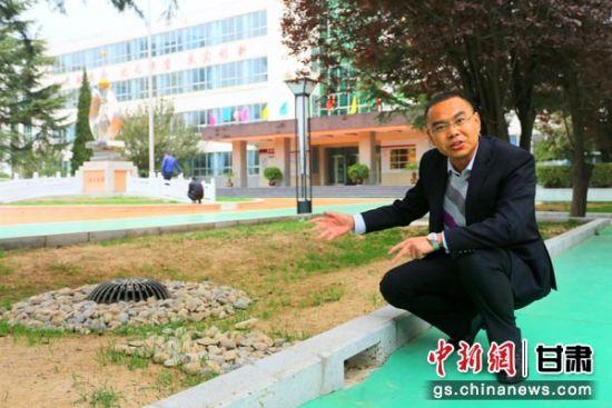 图为庆阳市团结小学校长齐建伟向记者介绍改造后的低洼雨水井。