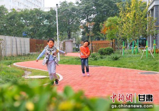 图为庆阳当地小朋友正在改造后的小区花园里嬉戏打闹。