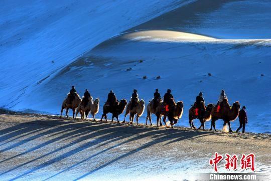 """图为游客骑骆驼穿行于""""沙雪""""间。(资料图) 张晓亮 摄"""