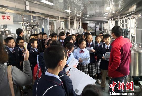 图为小学生参观食品加工工序。 刘玉桃 摄