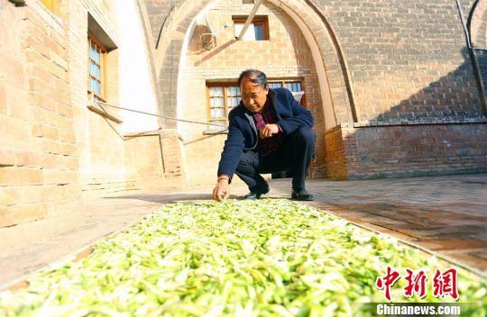 庄头村小河湾组村民金书荣正在自家农家乐院里晾晒萝卜干。 高展 摄
