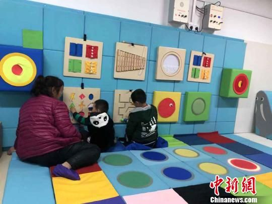 """在定西博爱医院""""集善残疾儿童助养项目""""资助的多感官康复训练室里,家长正陪着孩子训练。 王祖敏 摄"""