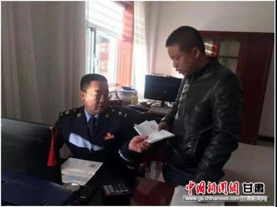 图为陈祯林为纳税人解决发票问题。
