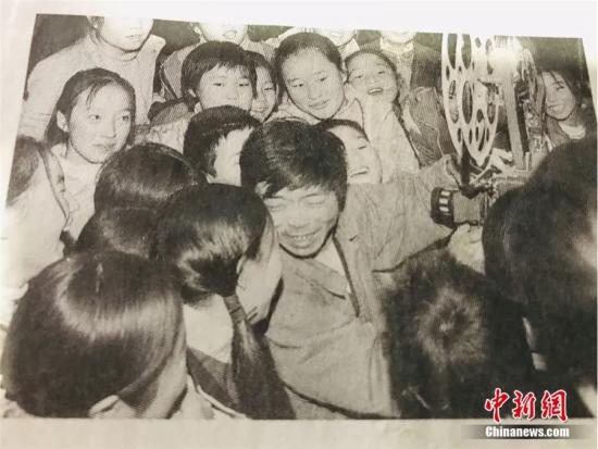 图为尹凤民正在放电影,他被一群孩子围在中间。(翻拍于报纸)闫姣 摄