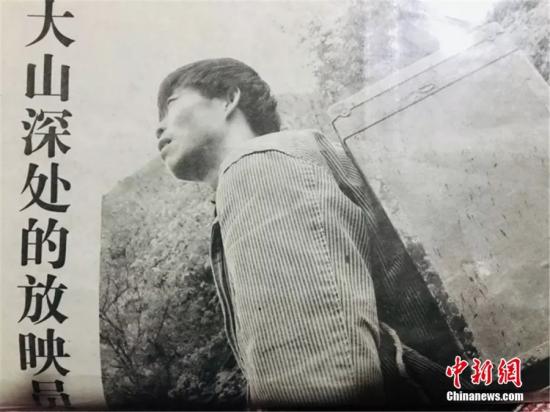 图为尹凤民背着电影设备。(翻拍于报纸)闫姣 摄
