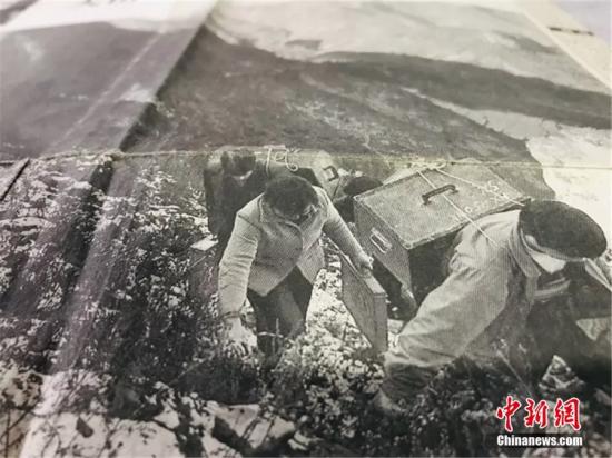 """图为尹凤民和妻子""""翻山越岭"""",背着沉重的设备为村民们放电影。(翻拍于报纸)闫姣 摄"""